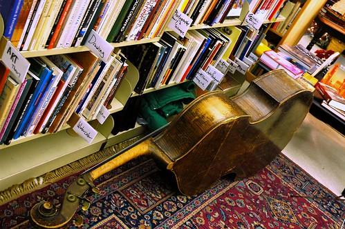 Bass cello waits next to racks of used books organized by subject, in Abraxus Books, Ballard, Seattle, Washington, USA