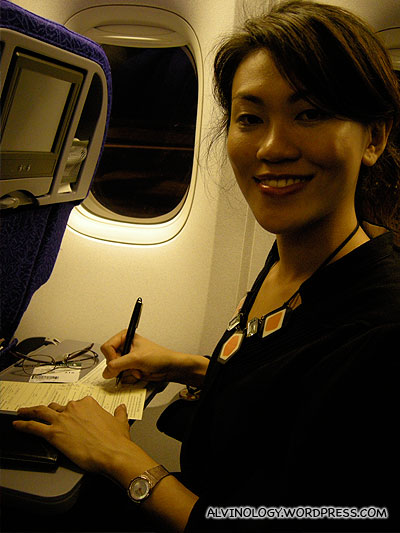 Rachel writing her diary while on board our SQ flight