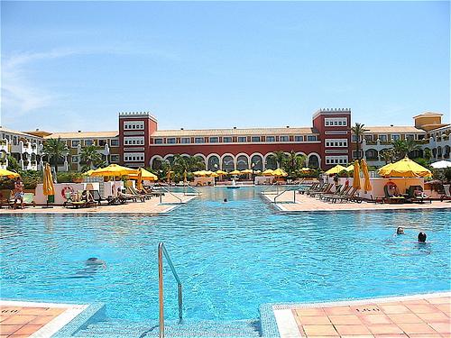 Vista de la piscina con el hotel al fondo