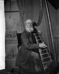 man seated at a harp