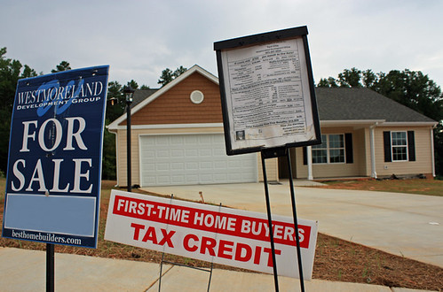 A sign promoting the home buyer tax credit in front of a home