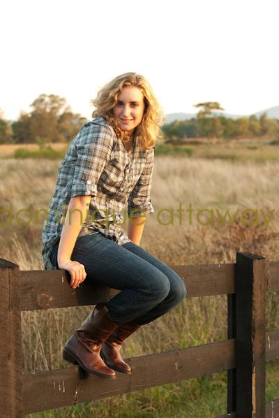 girl senior sitting on fence