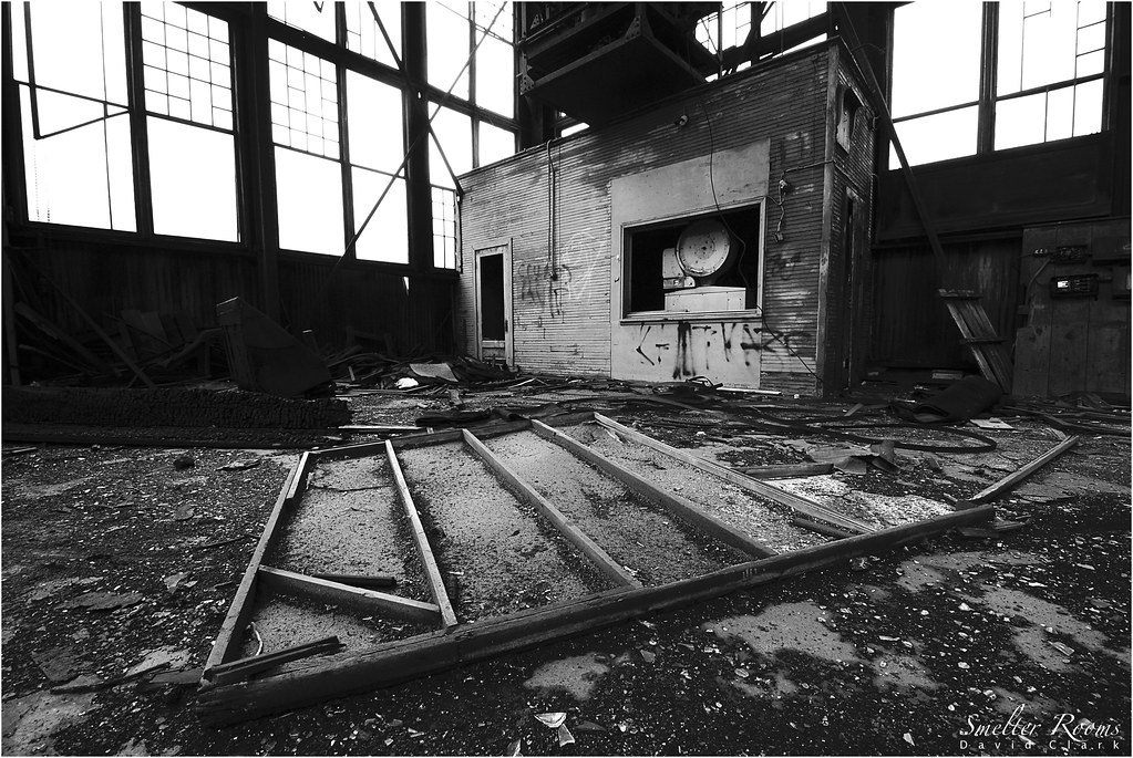 A black and white composition of a small machine room within a large room, surrounded by debris.