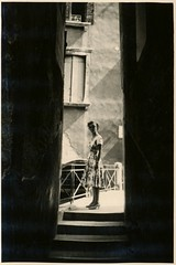 She felt the lure of dark spaces (liquidnight) Tags: old travel people blackandwhite bw woman monochrome lady stairs portraits vintage found photo alley darkness snapshot steps collection photograph alleyway 1950s mysterious vernacular passage photos found