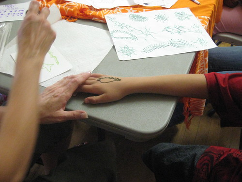 Henna is applied to create a design on one childs hand.