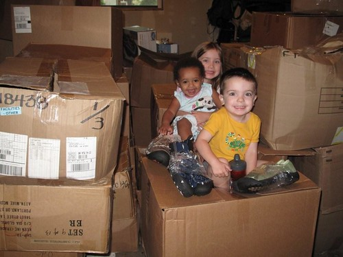 Finley, Amelie and Luc use boxes of donated KEENs as their own personal climbing gym.