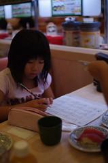 回転寿司で宿題をこなす萌
