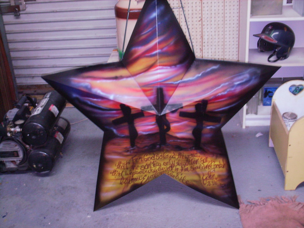 Calvary airbrushed on decorative tin star.