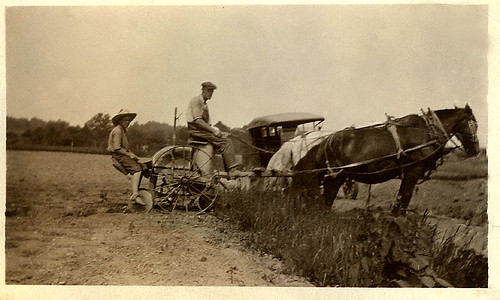 Old Photo. Man and boy on horse drawn farm equipment with old auto in background.