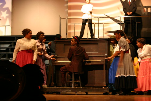 Coalhouse Walker (Rashad Williams, Fowler), center, plays ragtime music for his eager listeners and dancers.