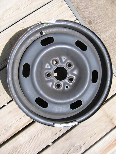 This is a photo of a steel wheel without a wheel cover or hubcap. Steel wheels are usually much heavier than aluminum and are black unless they have been styled or painted.