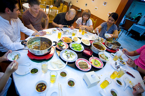 Friends enjoying Sichuan-style hot pot at Phai Khiaw, a restaurant in Bangkok's Silom district