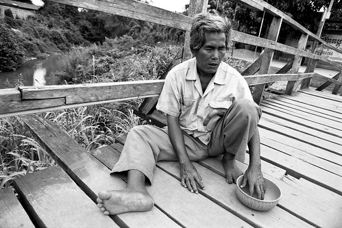 blind beggar on bridge - border town, Cambodia