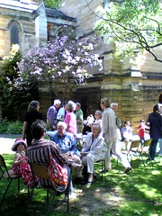 people on lawn outside Hunter Baillie Church, with Cherry Tree in blossom