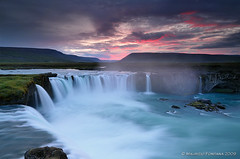 Godafoss sunset (Maurizio Fontana) Tags: road street travel blue light sunset sea sky orange color reflection fall water colors reflections d50 dark lights mirror fly waterfall iceland travels nikon strada tramonto mare colore blu volo waterfalls cielo land vulcan luci terra vikings viking acqua spa colori riflessi isle viaggi viaggio arancio luce vulcano arancione specchio isola belin riflesso vichingo godafoss cascate cascata islanda d300 tenebre goafoss vichinghi rgmfc expressyourselfaward