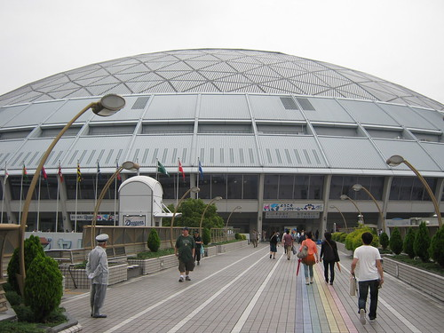Home of the Chunichi Dragons! I wonder why that older Japanese guy is dressed like a bellhop/limo driver and standing outside the stadium.
