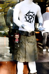 """Sadie keeps up with Seattle fashion trends by posing outside the """"Utilikilts"""" store"""
