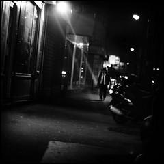 Passer-by & nighly ray (:n:) Tags: street city shadow bw blur paris france cold night walking blackwhite blurry dof nightshot pavement olympus 50mm14 nb zuiko filmnoir 75019 marxdormoy