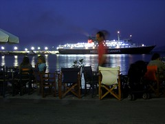 RUNNING LIFE IN THE DARK (dimitra_milaiou) Tags: life road blue sea summer sky people moon black water silhouette night port reflections dark landscape boats island greek lights boat europe ship view chairs sony north ikaria hellas tourist east greece moonlight summertime emotions ports ouzo dimitra hellenic  evdilos dscp93a seaways   aigaio ouzaki  milaiou