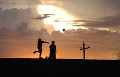 Sunset Football (Kid Gibson) Tags: sunset orange sun storm weather kids clouds canon children rebel football glare play dynamic god sigma glorious ala xsi pigskin powerpoles 28105mm spanishfork