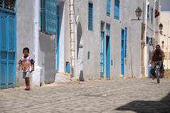 Walking boy and cycling man in Kairouan's medina (Alexandre Moreau | Photography) Tags: street trip blue windows summer people sun white man hot bike horizontal rural photography nikon doors colours child tunisia calm tradition t 2009 onthemove tunisie walkin kairouan cylcing d90