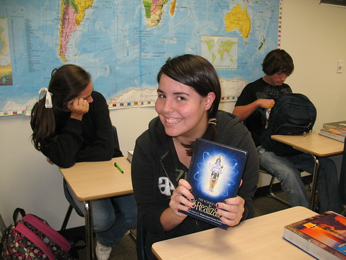 High School Student happily shows her book