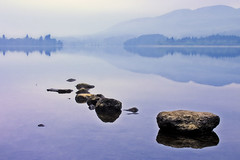 A very still Lake of Menteith (Stuart Stevenson) Tags: blue trees mist lake mountains reflection water misty canon scotland still rocks silent canon300d stirling earlymorning calm stuart homecoming serene menteith lakeofmenteith trossachs tranquil hdr scotchmist homecomingscotland stuartstevenson stuartstevenson