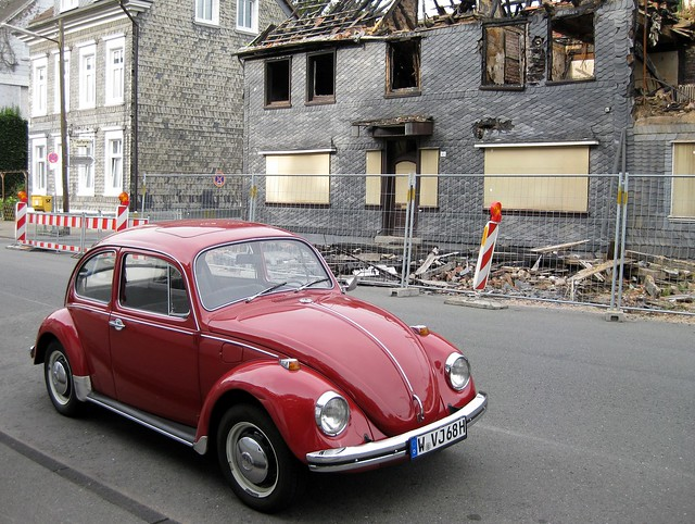 What we saw on our cycling tour: red Volkswagen beetle in front of burned house