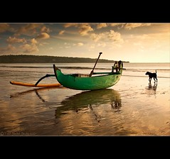 Ready to Roll. Jimbaran Bay - Bali, Indonesia. (tsechel) Tags: sunset bali dog reflection beach water night clouds indonesia bay fishing indianocean paddle shift canoe handheld jimbaran outrigger canon50d leefilters 54days