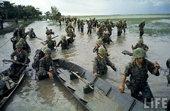 S.Vietnamese soldiers wading into canal to put equipment in boats to lure Vietcong guerrillas from nearby flooded paddies during Vietnam War. 1962 par VIETNAM History in Pictures (1962-1963)