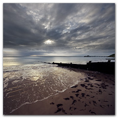 Did someone just shave a monkey on the beach? (s0ulsurfing) Tags: ocean wood shadow sea sky cloud seascape reflection texture tourism beach water weather silhouette clouds composition landscape island evening bay coast pier vanishingpoint wooden seaside twilight sand waves skies qu