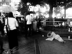 57/365: Homeless Angel in Shibuya (joyjwaller) Tags: blackandwhite beauty japan angel night tokyo newspaper neon homeless shibuya serenity crowds homelessman japaneseman project365