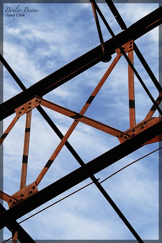A semi-abstract composition of sky with rusty beams in a geometric arrangement.