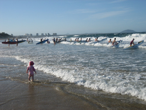 A kayaker club prepares to launch into the surf
