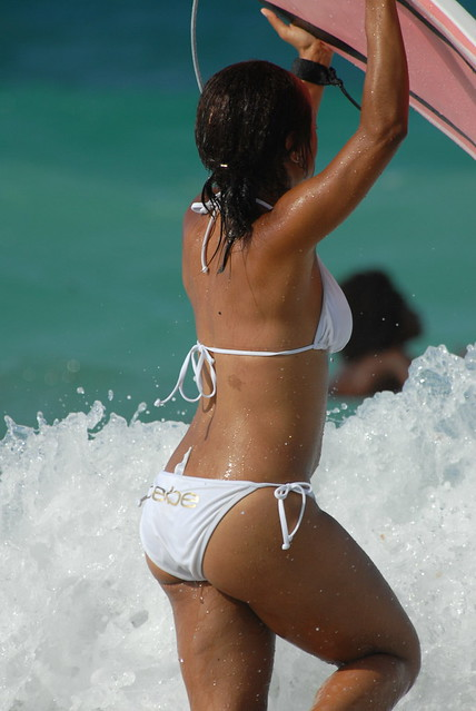 Girl on the beach in white bikini surfing