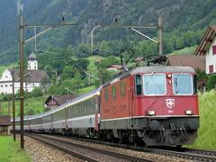 SLMNr 4765 : SBB Lokomotive Re 4/4 II 11203 / SBB Re 4/4 420 203 mit Kirche Amsteg , Kanton Uri , Schweiz (chrchr_75) Tags: hurni christoph schweiz suisse switzerland svizzera suissa swiss kanton uri reuss reusstal gotthard gotthardbahn nordrampe sbb cff ffs schweizerische bundesbahnen bundesbahn chrchr chrchr75 chrigu chriguhurni zug train juna zoug trainen tog tren поезд lokomotive паровоз locomotora lok lokomotiv locomotief locomotiva locomotive eisenbahn railway rautatie chemin de fer ferrovia 鉄道 spoorweg железнодорожный centralstation ferroviaria bestofgotthardnord kirchesilenen silenen urner kantonuri kirche church eglise chiesa albumsbbre44iiiii re44 re 44 albumbahnslmschweizerischelokomotivundmaschinenfabrikwinterthur slm slmnr
