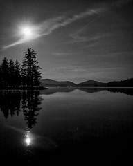 Midnight View (dmdzine) Tags: trees bw moon lake mountains nature water monochrome silhouette night clouds reflections stars darkness eerie adirondacks backpacking silence wilderness 11pm otherworldly pharaohlake almostmidnight moonburst moonflare pharaohlakewilderness silverefexpro