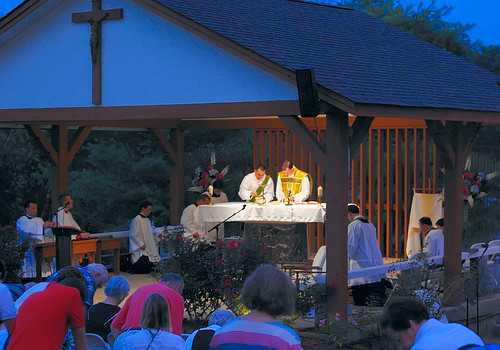 Outdoor novena at the Discalced Carmelite Novena, in Ladue, Missouri, USA - priest and deacon prepare for communion