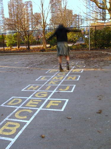 Young student playing hopscotch in an inner city school yard