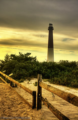 Barnegat Lighthouse (Maurizio Photography) Tags: statepark wood travel light summer vacation sky favorite lighthouse nature clouds digital canon fence newjersey interestingness sand scenery background perspective picture atlantic sharp explore crisp longbeachisland railing highlight description hdr barnegatlighthouse comment foreground barnegatlight beachhaven oldbarney goldtones rebelxsi canoneosdigitalrebelxsi mauriziophotography