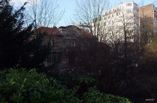Derrière les arbres, de l'autre coté de la rue, on aperçoit la maternelle du quartier.