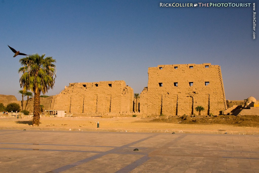 Sunset illuminates the front of Karnak Temple, near Luxor, Egypt, with a warm glow.