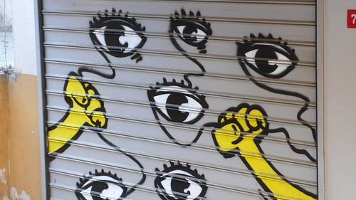 graffiti fromm Istanbul: two yellow hands holding the strings of balloon eyes
