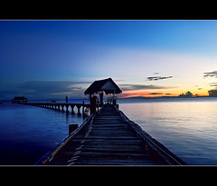 the blues..with a pinch of red,orange and yellow.. (PNike (Prashanth Naik)) Tags: sunset red sea sky orange sun water yellow pier nikon asia southeastasia philippines bluesky bluehour reflectioninwater nalusuanisland d3000 colorsinwater endlesspier pnike