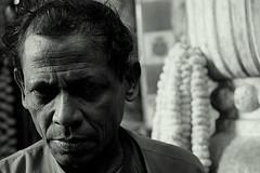 looking? | Kolkata (arnabchat) Tags: light portrait india man flower monochrome face look dark eyes market kolkata bengal calcutta bangla westbengal duallight canon400d arnabchat mullickghat arnabchatterjee mullickghatflowermarket