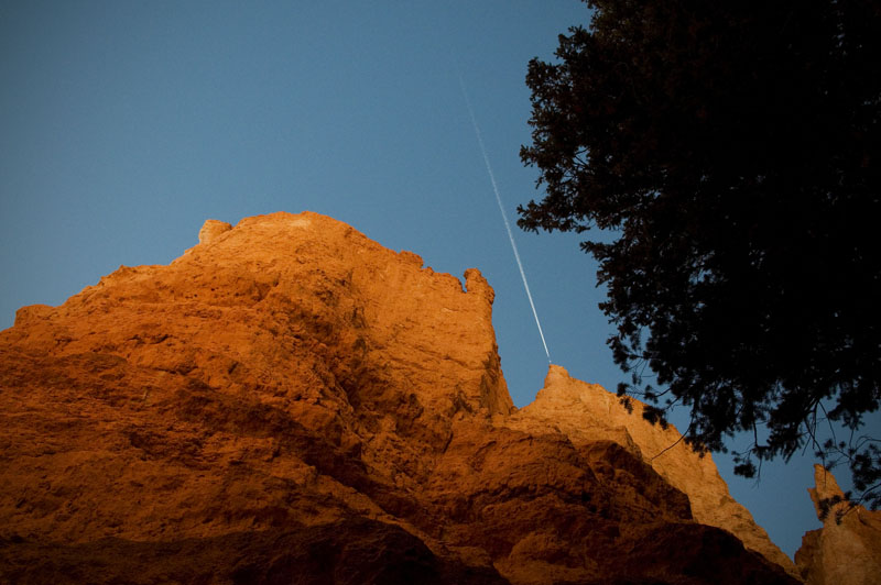 A plane streaks across the sky above the Wall Street portion of the Navajo Trail as I streak across the lower portion of the trail.  Streak as in moving fast not as in naked... park rules.