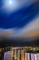 Clouds dance under a full moon (Xavier Donat) Tags: city longexposure brazil sky urban moon brasil riodejaneiro night clouds contrast buildings stars landscape lights moving cityscape wind perspective wideangle nopeople bynight fullmoon explore shining 30s leblon explored