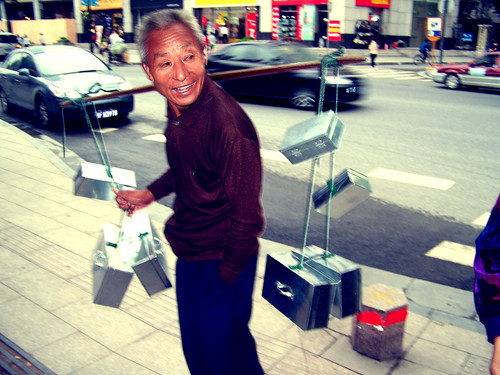 Chinese man on pavement, holding silver metallic boxes