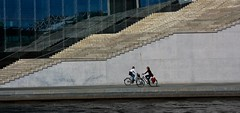 Two Bikes (Leon Sammartino) Tags: red berlin architecture modern stairs cyclists smash riverside bikes backpack saddle newwave collision chicksonbikes ladiesonbikes