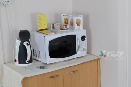 電熱壺、微波爐和櫃子內很齊全的餐具